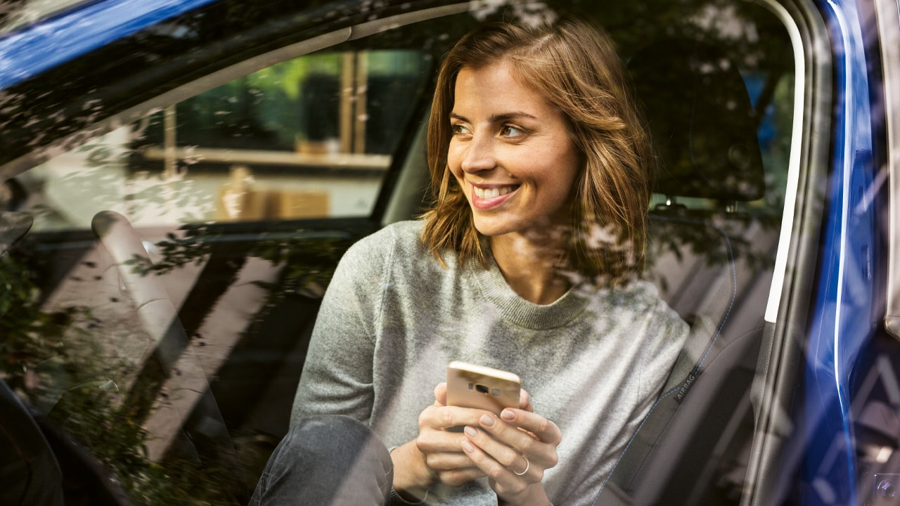 woman sitting in car holding a mobile phone