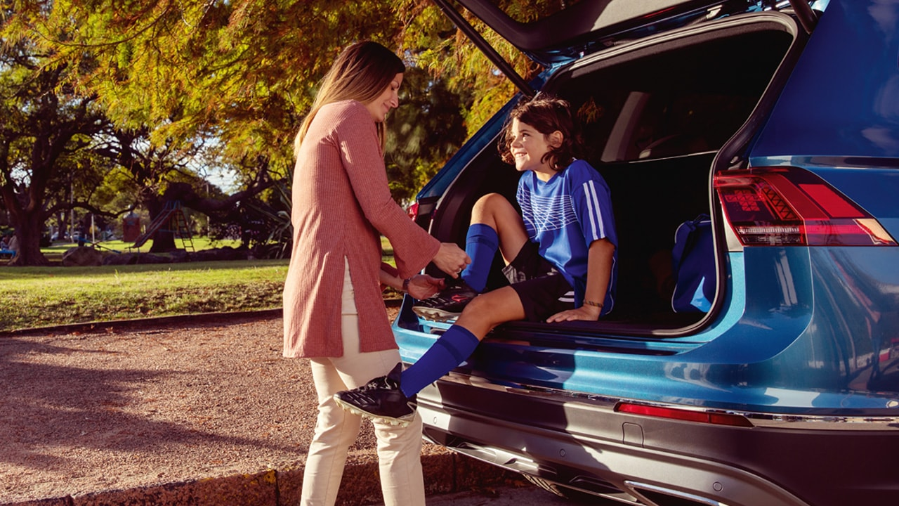 A young girl sitting in the trunk of VW SUV while her mom helps to tie a shoe